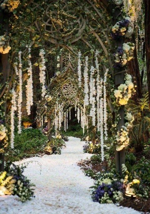 a unique pathway to the ceremony or reception space with arches with vines and floral garlands hanging down
