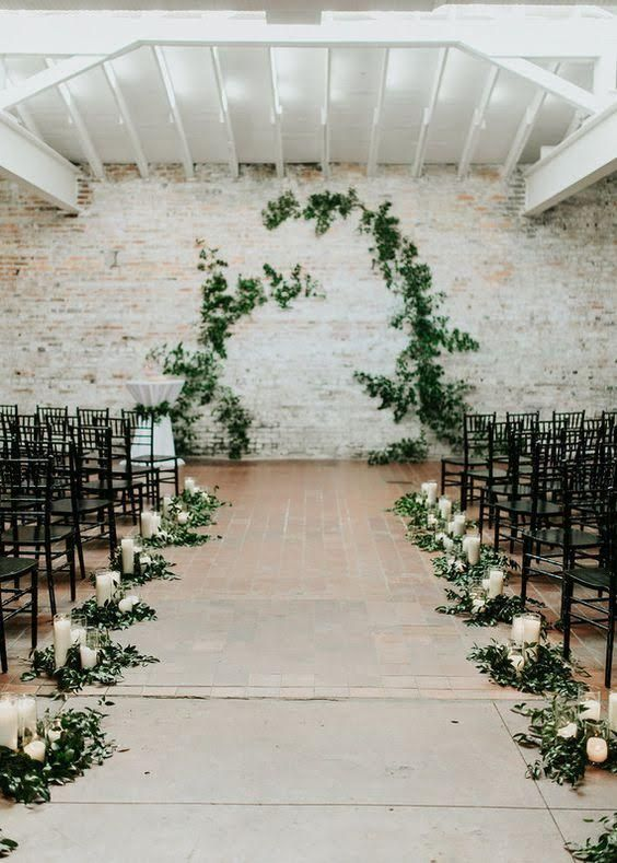 laconic decor with greenery, candles and black chairs will make your walking down the aisle stylish