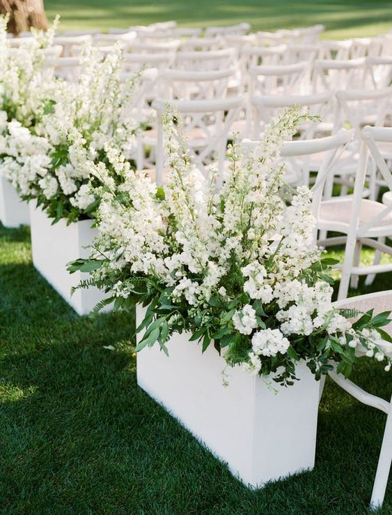 white chairs and white planters with greenery and white blooms make up a chic and stylish modern wedding aisle
