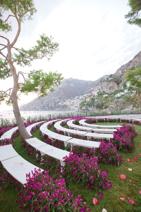 a modern and super bold wedding aisle with white semi circle benches and bright purple blooms lining them