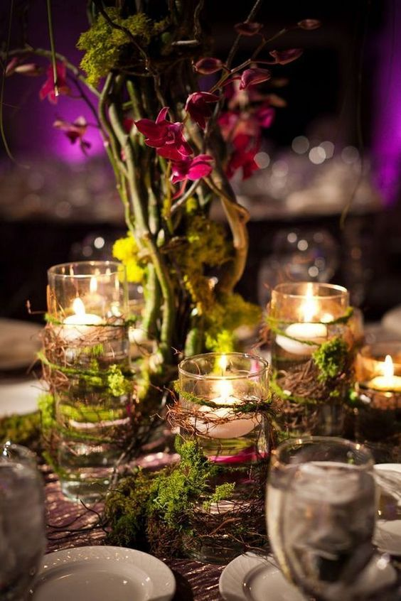 an enchanted forest wedding centerpiece with candles wrapped with vine and moss and some vines with blooms next to them