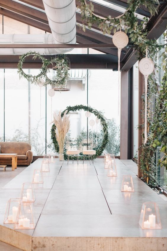 a modern meets boho wedding aisle with geometric candle lanterns and candles, pampas grass and greenery
