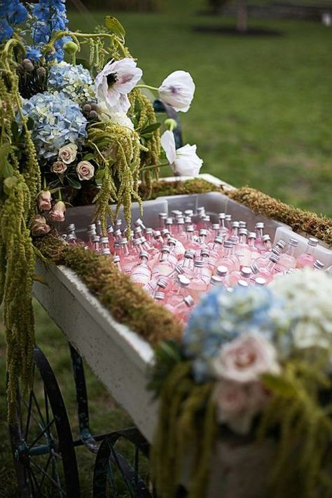 an enchanted forest wedding drink station with a cart decorated with moss, pastel blooms and greenery