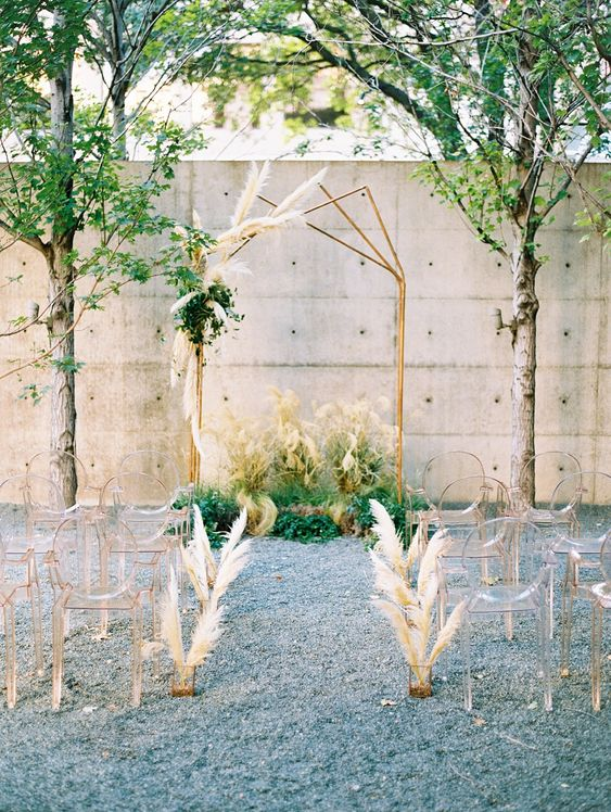 a modern meets boho wedding aisle with ghost chairs, pampas grass arrangements and a matching arch with pampas grass