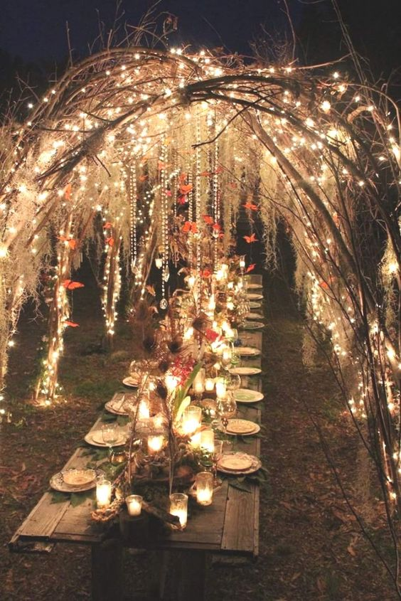 an enchanted forest wedding reception under vine arches decorated with lights and red origami garlands plus candles and red blooms on the table
