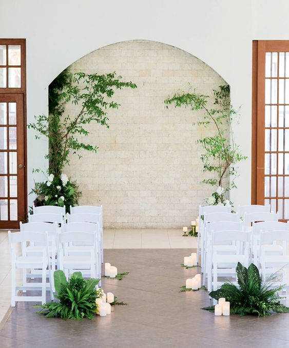 a modern tropical wedding aisle with lush tropical greenery and candles brings an outdoor tropical feeling indoors