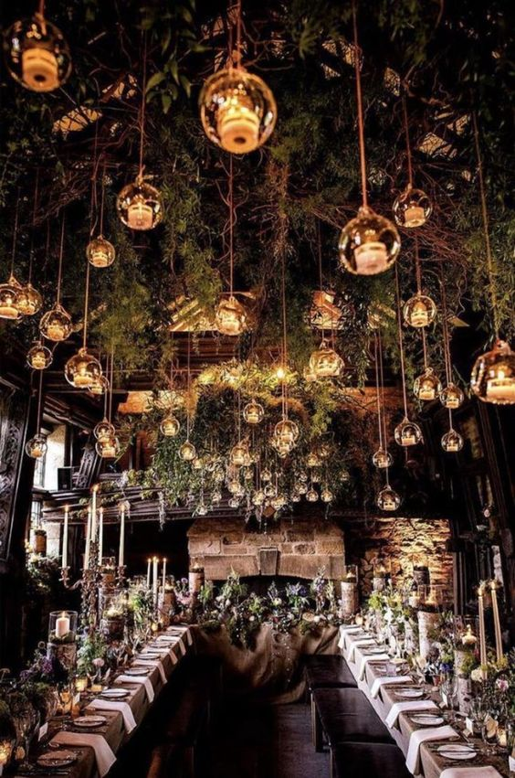 create an enchanted forest ambience inside with branches and greenery hanging down and candle lanterns all over