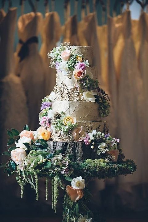 a birch bark wedding cake placed on a tree stump with blooms and greenery and decorated with florals and greenery, too
