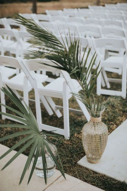 a modern tropical wedding aisle with white chairs and palm leaves in clear and wicker vases for a stylish and simple look
