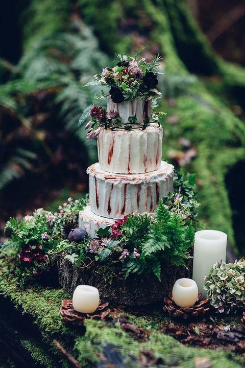 a buttercream wedding cake with fresh greenery and dark blooms, one a tree stump with ferns, blooms and candles