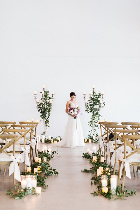 a stylish modern meets rustic wedding aisle with greenery, candles and chairs accented with elegant white ribbon bows