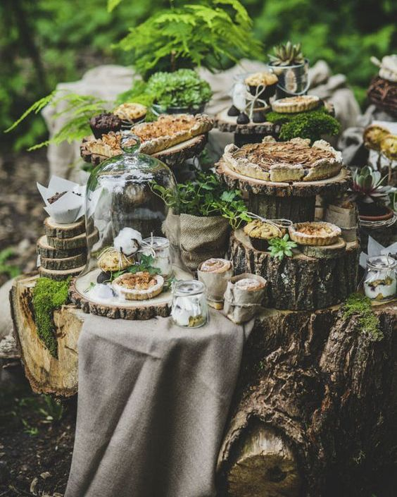a dessert table perfectly styled for the theme with tree stumps and wood slices, pies and tarts in cloches and lots of greenery and moss