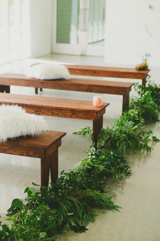 wooden benches paired with lush greenery and fluffy pillows to create a fresh and welcoming ambience