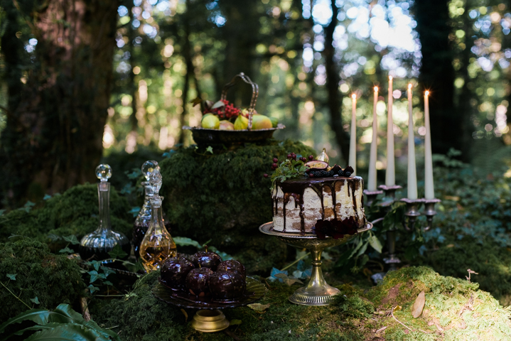 an adorable enchanted forest wedding dessert table with a semi naked wedding cake, fruits, alcohol, candles