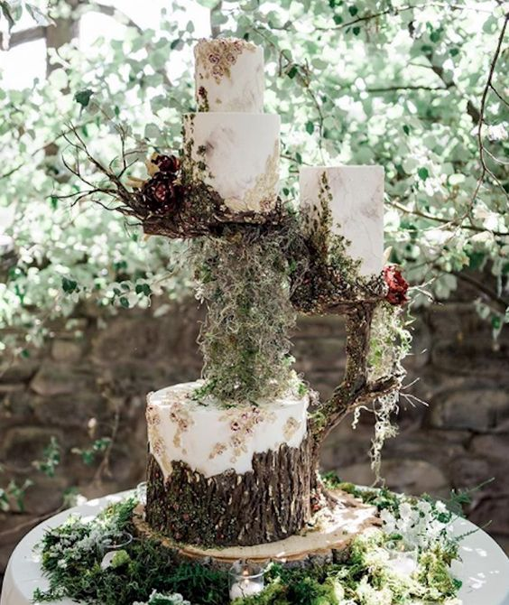 an enchanted forest wedding cake arrangement with a tree stump and a greenery holder with nests with two wedding cakes and lots of blooms and greenery
