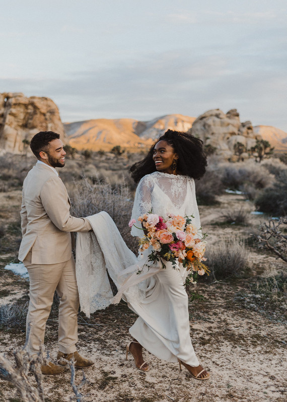 The bride was wearing a slip dress with a lace cape, nude heels and the groom was wearing a neutral suit with a floral tie and neutral boots