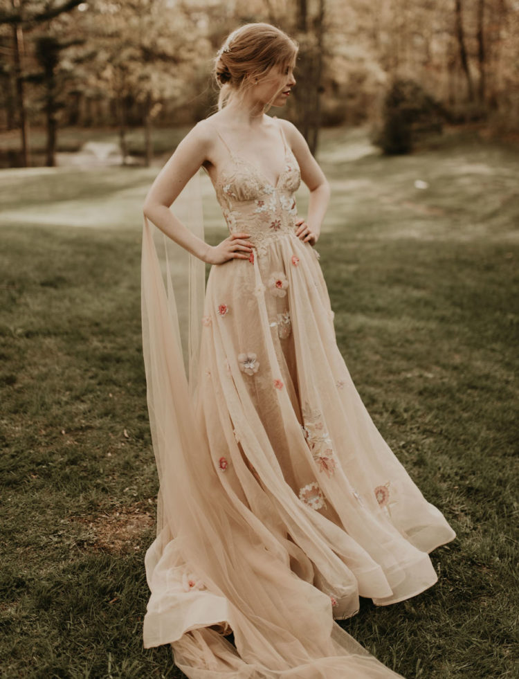 The bride was wearing a beautiful nude wedding dress with floral appliques, a gauzy skirt, an open back and a capelet