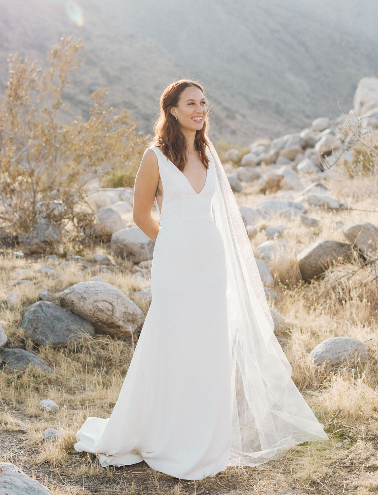The bride was wearign a plain minimalist wedding dress with a deep V neckline and a long veil