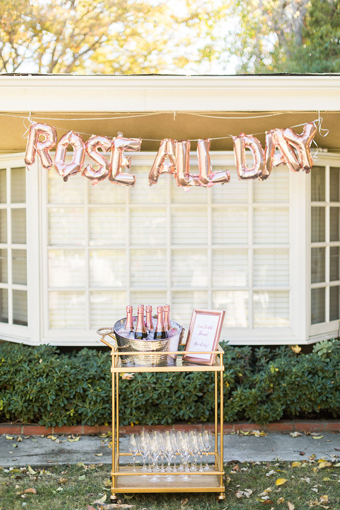 The drink station was done with a gold bar cart, glasses and bottles, a rose gold balloon garland over it