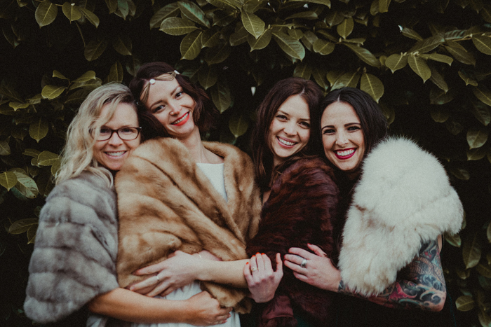 The bride and bridesmaids covered up with faux fur of different colors