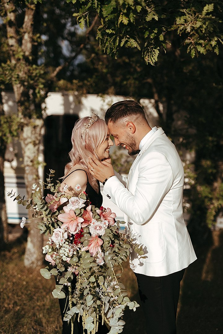 The bride was rocking pastel pink hair and was carrying a gorgeous pink and blush bouquet with greenery