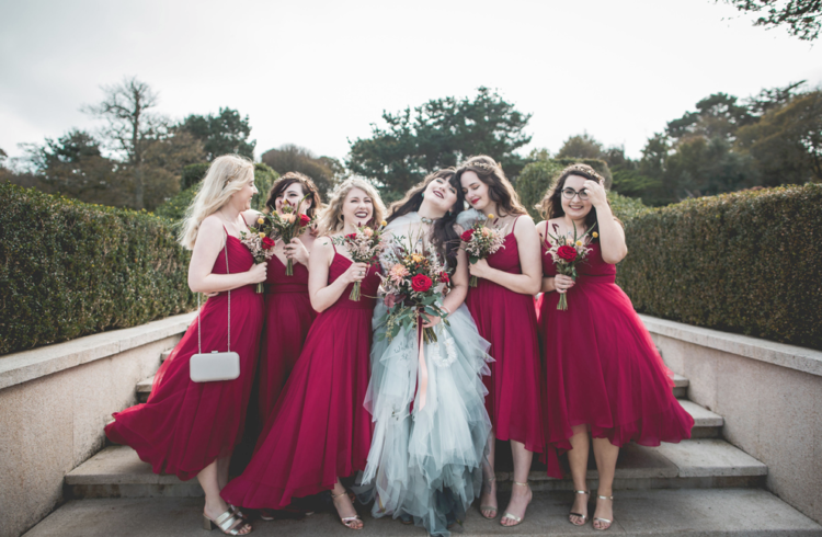 The bridesmaids were wearing burgundy spaghetti strap high low dresses and silver shoes