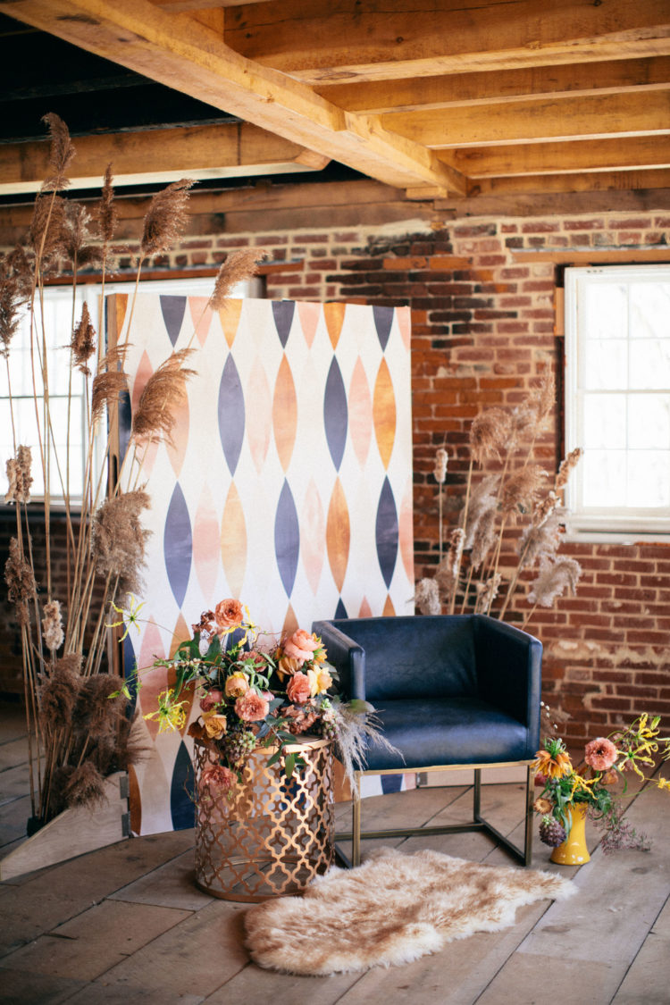 The lounge was done with a mid-century modern backdrop, a fur rug, a navy chair and dried herbs and leaves