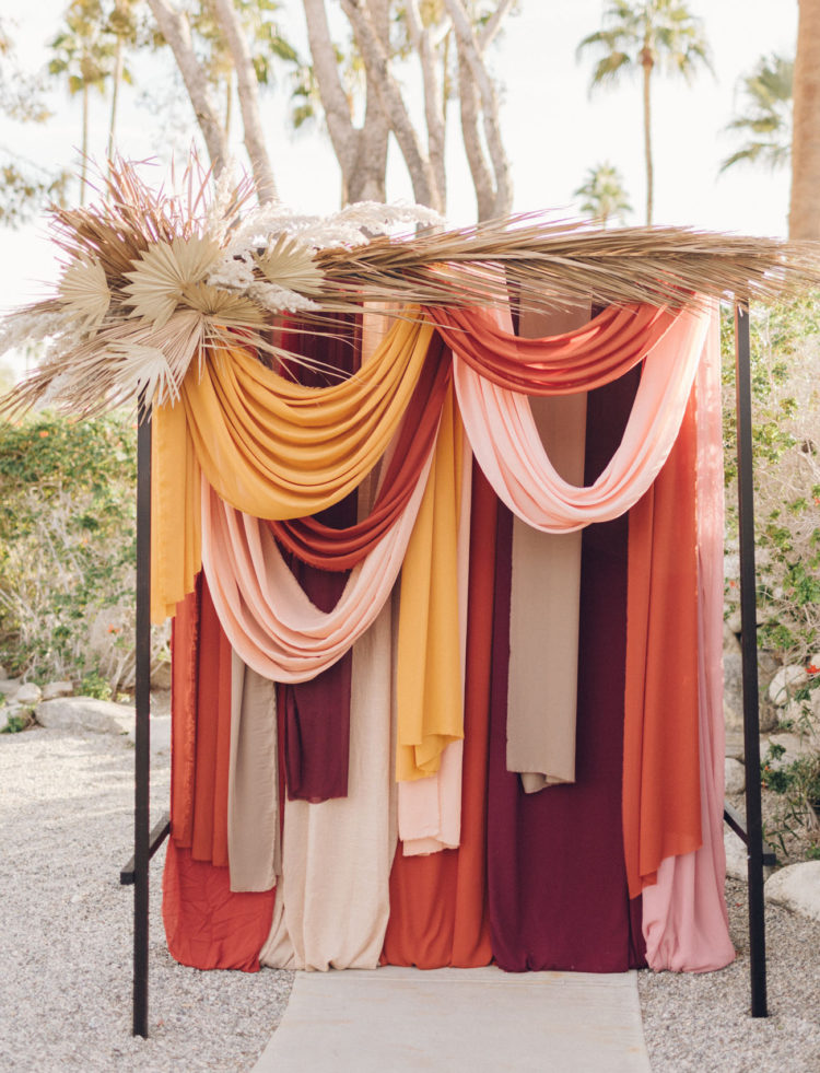 The wedding backdrop was done with muted and bright fabric hanging and dried leaves and herbs