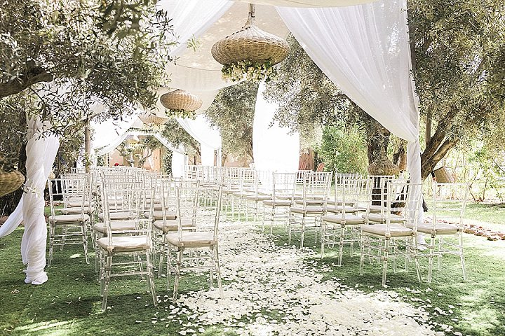 The wedding ceremony space was done with white curtains, white petals,sheer chairs and beautiful olive trees