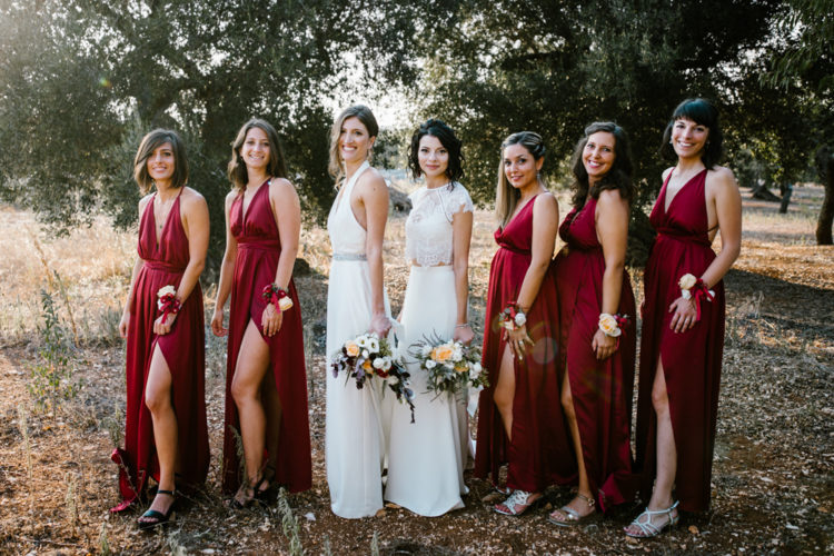 The bridesmaids were wearing burgundy maxi dresses with slits and floral corsages