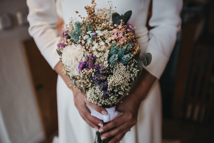 The wedding bouquet consisted of dried blooms and greenery, herbs and foliage and a right amount of purple and lilac