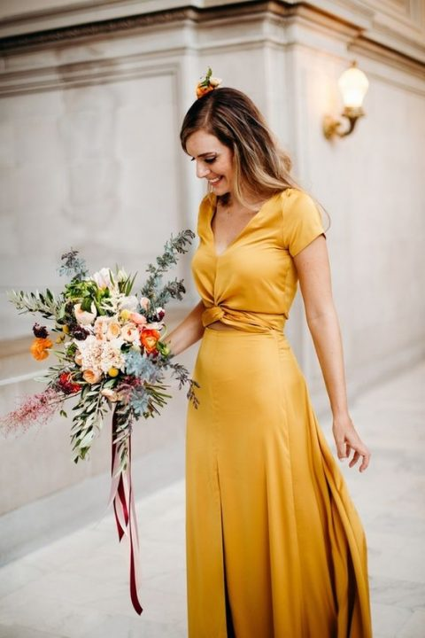 a marigold wedding gown with a V-neckline, a layered skirt and a tied bodice with short sleeves for a city hall ceremony