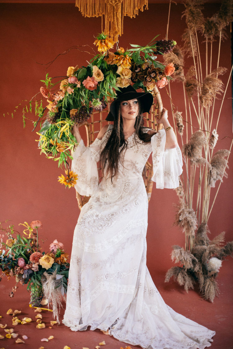 The second bridal look was done with a beautiful embroidered wedding dress with a cold shoulder and a black hat