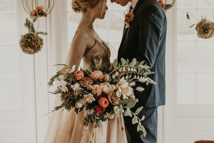 The wedding bouquet was lush and textural, with peachy, burgundy, neutral blooms and greenery