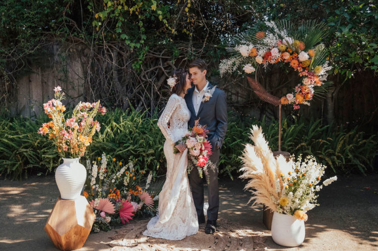 The wedding ceremony space was done with pampas grass, dried and colorful blooms, geometric touches and fronds