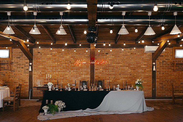 The wedding venue was an industrial barn decorated with lights and a neon sign