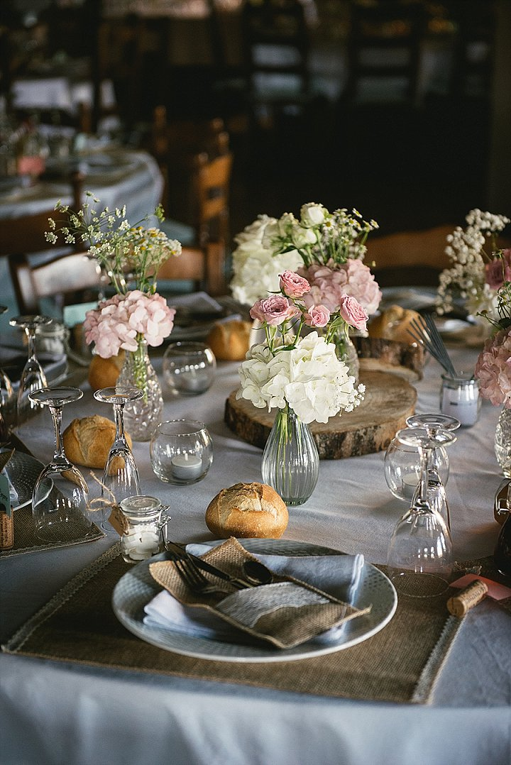 The table decor was done in a simple way, with burlap placemats and pockets, simple neutral and pink blooms and wood slices