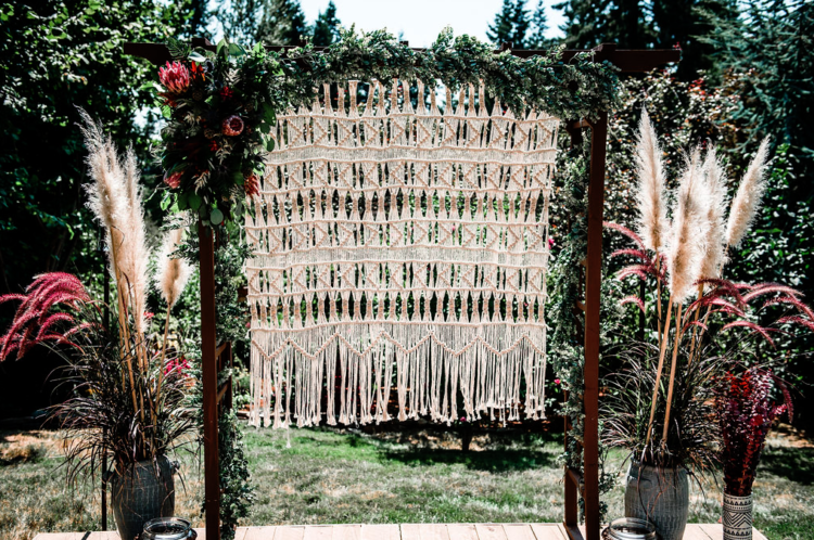 The wedding backdrop was a macrame one, with greenery and king proteas, with grass arrangements on both sides