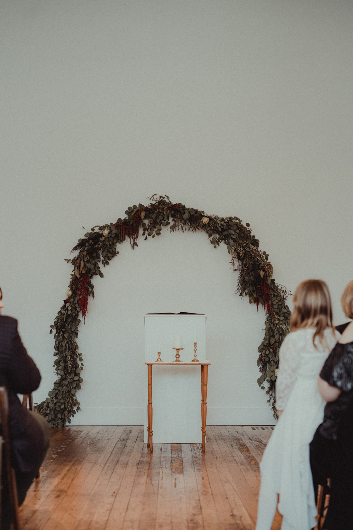 The wedding ceremony space was done casual, with a single greenery arch and some blooms