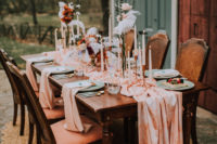 07 The wedding tablescape was done with a dark stained table, a pink table runner, candles, blush roses and king proteas plus feathers