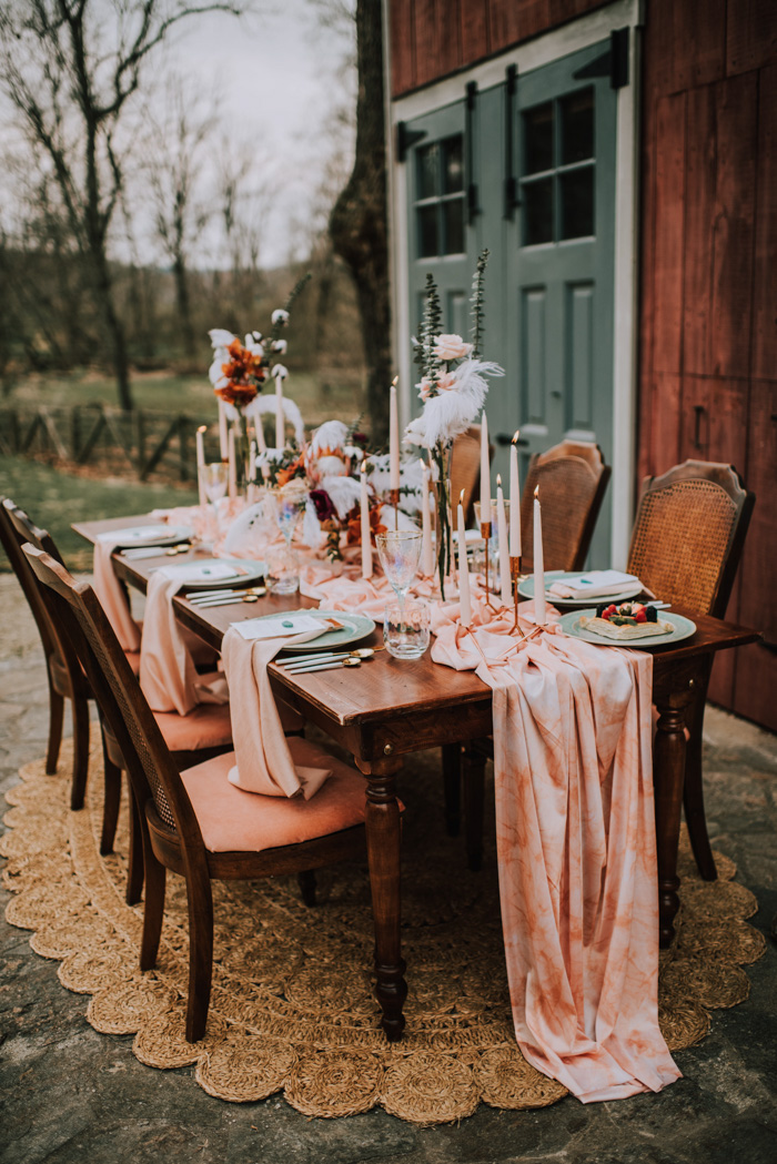 The wedding tablescape was done with a dark stained table, a pink table runner, candles, blush roses and king proteas plus feathers