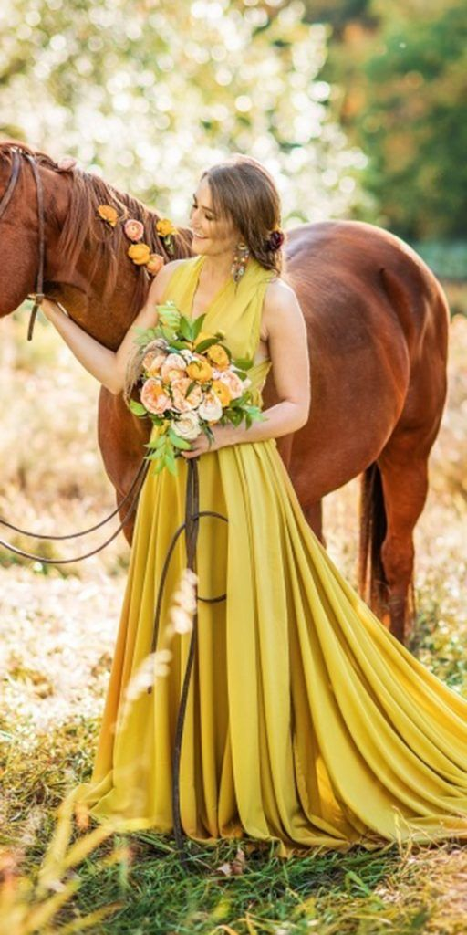 a mustard A-line wedding dress with a wide strap bodice, a pleated A-line skirt with a train