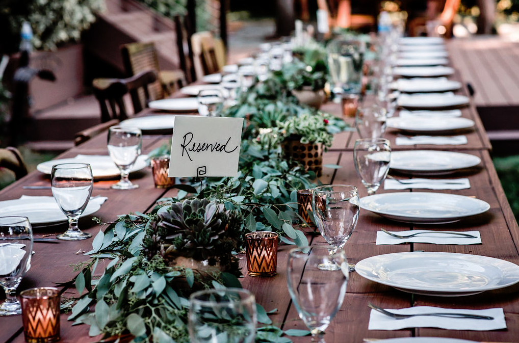 The tablescape was done with much greenery, succulents, candles and neutral porcelain