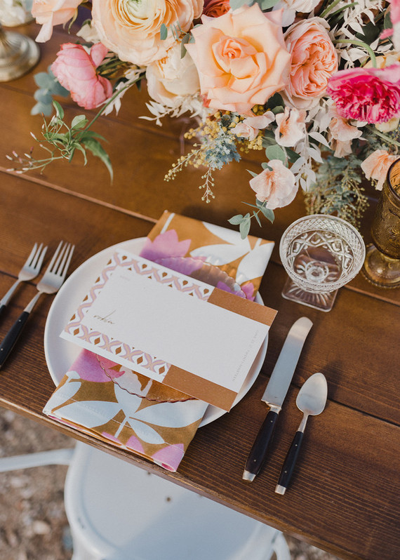 The wedding tablescape was done with bright florals, bright cards and napkins in the colors of the wedding shoot