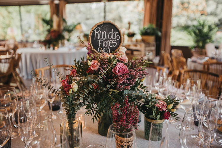The wedding tablescape was done with pink blooms, greenery and a chalkboard table number