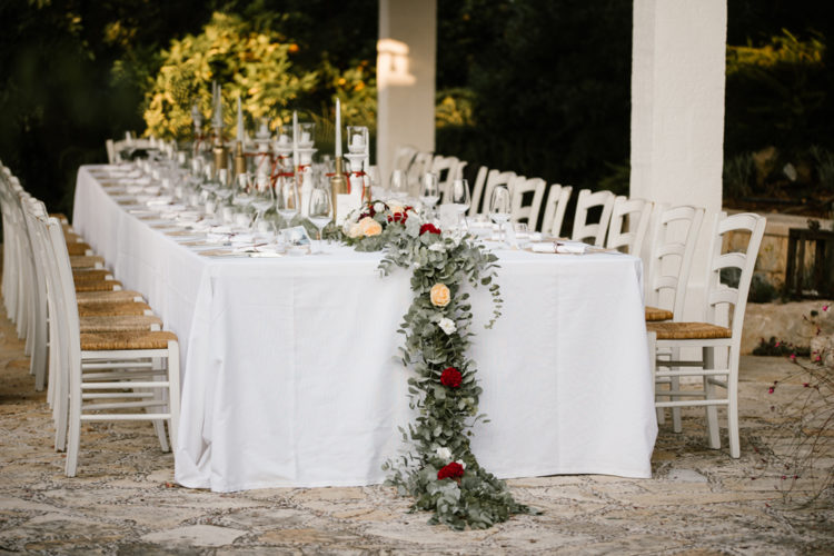 The wedding tablescapes were done with greenery and bright bloom runners, lanterns and candles