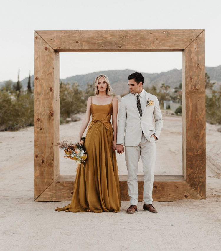 a mustard modern wedding dress with spaghetti straps, a pleated skirt and a tied waistline plus a cutout back
