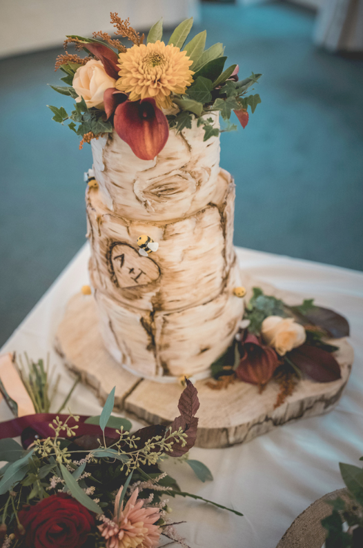 The wedding cake was covered with bark, bees and topepd with fresh blooms and greenery