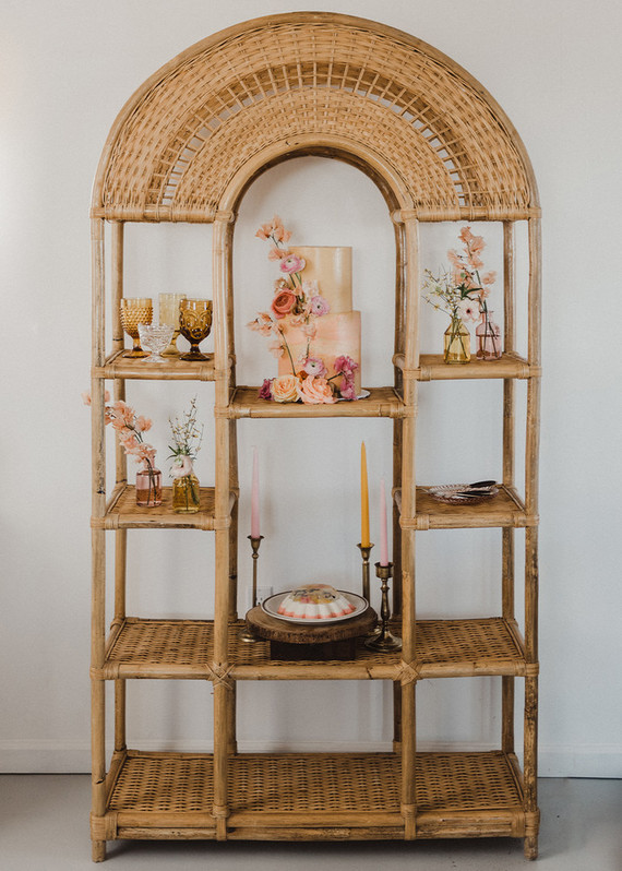 What a lovely way to display your wedding cake - a dessert table on a large wicker storage unit