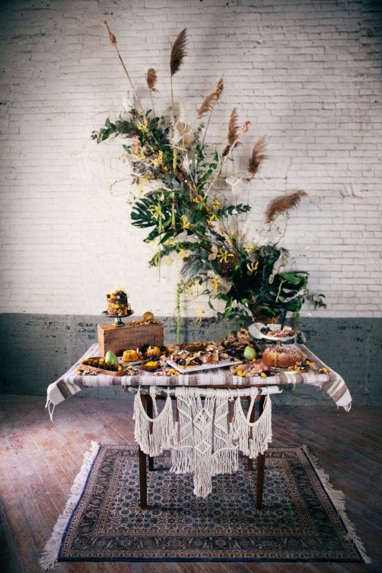 The table was decorated with macrame and there is a gorgeous lush greenery and dried flowers backdrop